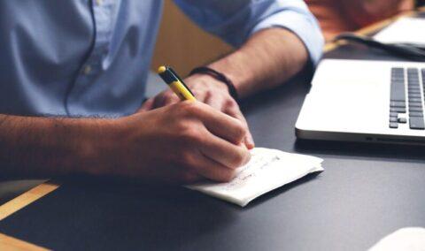 writing next to laptop