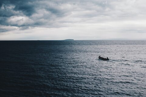 Boat sailing into a dark stormy sea - photo: Unsplash