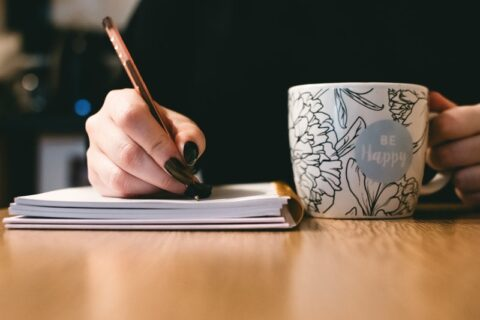 Woman writing in notebook with coffee mug to one side