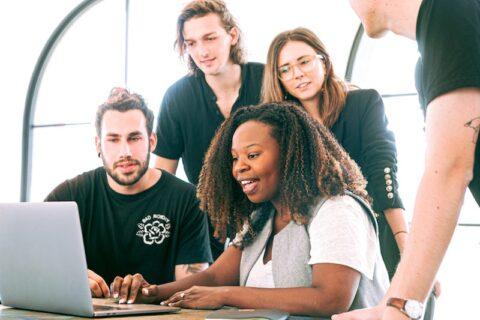 Team gather around computer.